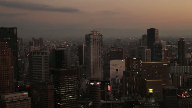 Buildings stand illuminated at dusk in Osaka Japan on Monday Oct 9 People are silhouetted as they take photographs at the Umeda Sky Building...