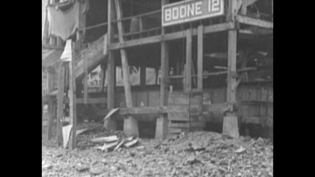 buildings surrounded by a troop train / numerous federal troops milling about / boone 12 on a sign on a damaged building passed by soldiers walking... - 発電所関係の職業点の映像素材/bロール