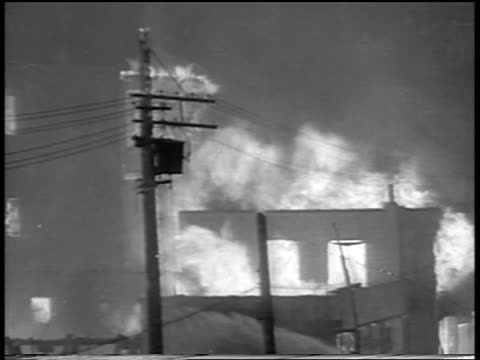 b/w 1934 buildings telephone pole on fire in chicago stockyard / newsreel - anno 1934 video stock e b–roll