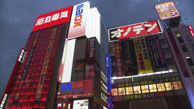 ws pan la buildings with neon signs, tokyo, japan - ネオンサイン点の映像素材/bロール