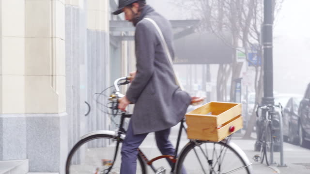 MS buisnessman wearing helmet commuting to work lifting bicycle up steps into office building