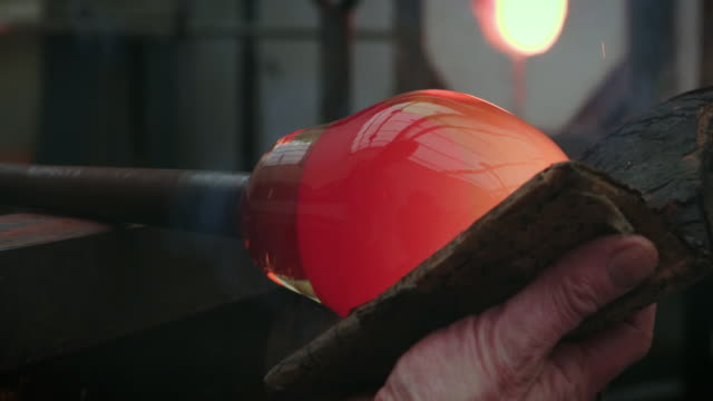 Bulb-like molten glass on a pipe is rolled and smoothed in a glassblowing workshop.