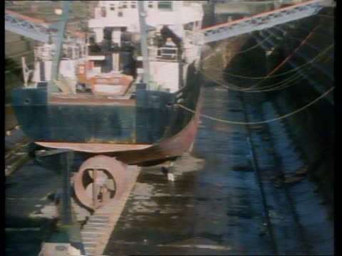 Bulk carrier Derbyshire inquiry Tyneside Swan Hunter Yard EXT TGV Ship in dry dock ZOOM IN as Peter Ridyard inspecting hull at stern