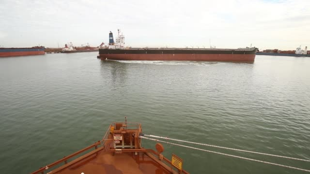 a bulk carrier is guided into port by tugs at fortescue metals group ltd's herb elliott port facility in port hedland australia on wednesday oct 26... - iron ore stock videos & royalty-free footage
