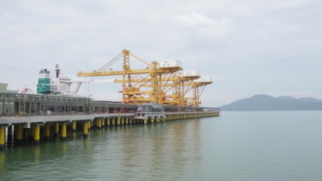 A bulk carrier ship sits berthed next to gantry cranes at the pier of Vale SAs Teluk Rubiah Maritime Terminal in Lumut Perak State Malaysia on Friday...
