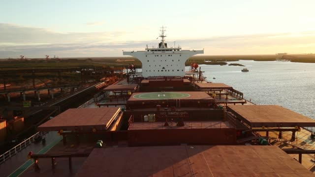 a bulk carrier sits moored at fortescue metals group ltd's herb elliott port facility as the sun sets in port hedland australia on wednesday oct 26... - iron ore stock videos & royalty-free footage