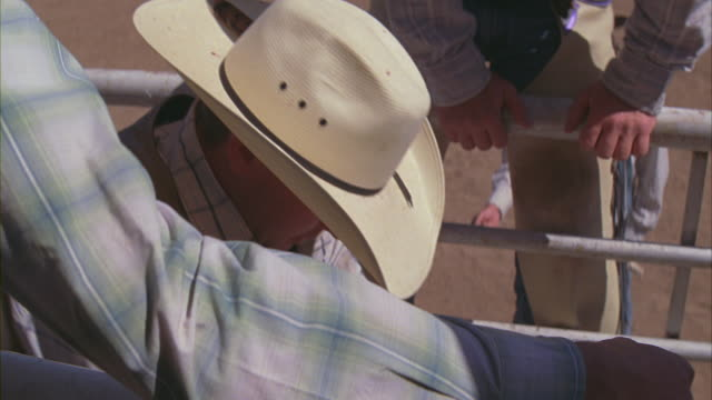 a bull rider climbs over a gate and prepares to ride his bull. - rodeo stock-videos und b-roll-filmmaterial