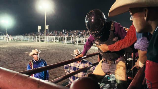 保護ヘルメットをかぶったブルライダーは、夜に人々でいっぱいのスタジアムでブルライディングイベントに出場する前に、動物のペンで雄牛に座る準備をします - ロデオ点の映像素材/bロール