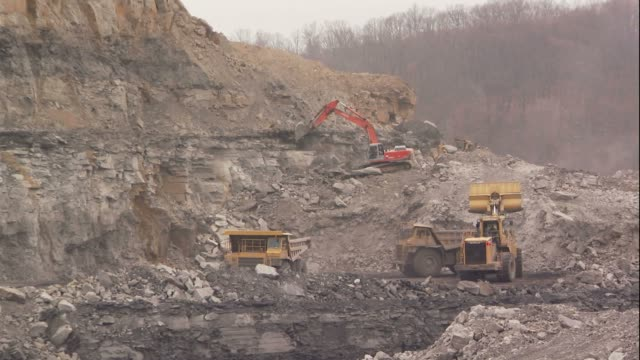 a bulldozer and dump truck operate at a coal strip mining site. - construction vehicle stock videos & royalty-free footage