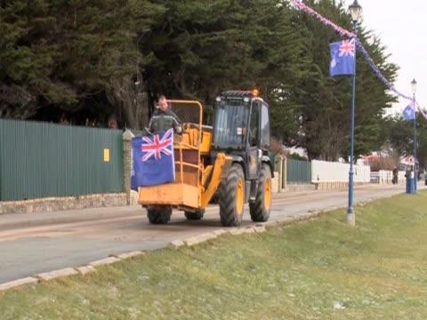stockvideo's en b-roll-footage met a bulldozer bearing the flag of the falkland islands moves along a road - atlantische eilanden