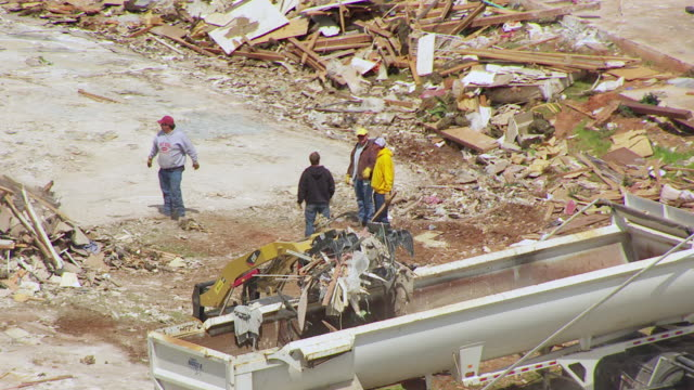 WS AERIAL ZO Bulldozer carrying debris at clean up site with people in background / Woodward, Oklahoma, United States