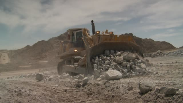 a bulldozer clears rocks and rubble at a quarry site. available in hd. - rubble stock videos and b-roll footage