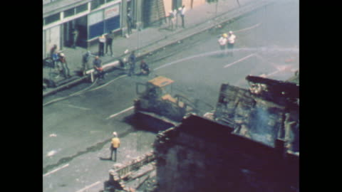 bulldozer completes destruction as firefighters hose a smoldering building / dazed onlookers watch from the opposing city street - 1967 stock videos & royalty-free footage