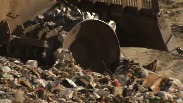 a bulldozer drives over garbage at a landfill. - gestione dei rifiuti video stock e b–roll