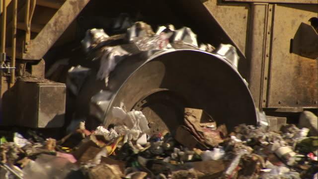 a bulldozer drives over trash at a landfill. - bulldozer stock videos & royalty-free footage