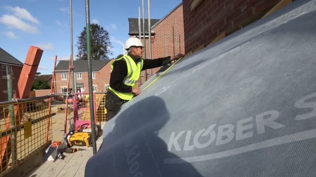 bulldozer moves around building site during construction at a bellway plc real estate site in northampton, u.k., on thursday, oct 10 a construction... - northampton stock-videos und b-roll-filmmaterial
