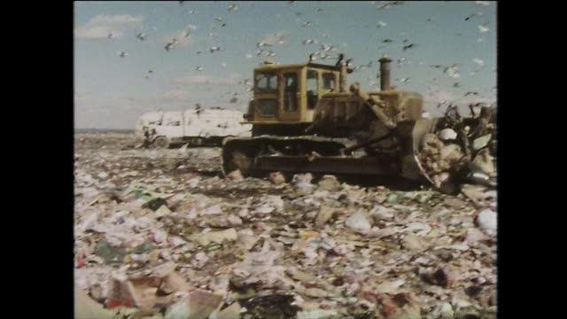 a bulldozer moves rubbish on a landfill site; new york, 1975 - 以前の点の映像素材/bロール