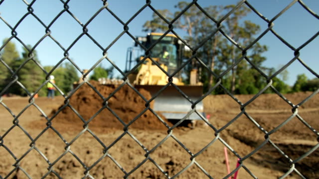 bulldozer moving earth towards fence - bulldozer stock videos & royalty-free footage