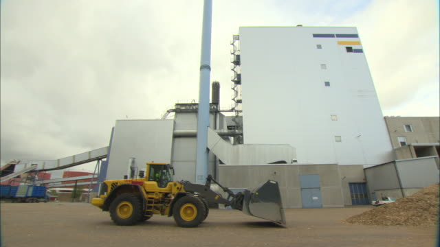 ws pan bulldozer moving large pile of woodchips outside biomass plant / vaxjo, sweden - vaxjo stock videos & royalty-free footage