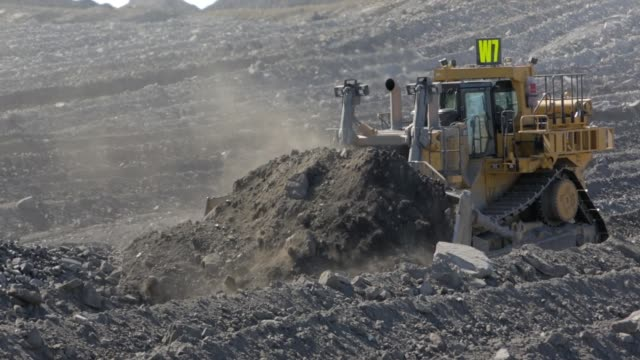 bulldozer moving mounds of dirt at a coal mine - earth mover stock videos & royalty-free footage