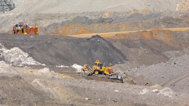 bulldozer moving mountains of dirt at a coal mine - iron ore stock videos & royalty-free footage