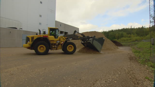 ws pan bulldozer moving pile of woodchips outside biomass plant / vaxjo, sweden - vaxjo stock videos & royalty-free footage