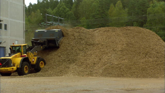 ws bulldozer moving pile of woodchips outside of biomass plant / vaxjo, sweden - vaxjo stock videos & royalty-free footage