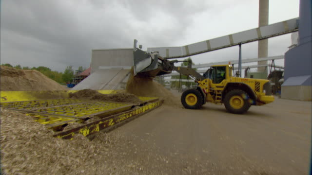 ws pan bulldozer moving pile of woodchips outside of biomass plant / vaxjo, sweden - vaxjo stock videos & royalty-free footage