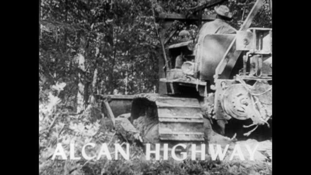 / bulldozer mowing down trees in a forest / 'alcan highway' flashes on screen / black worker and white worker shaking hands / road building and... - alcan highway stock videos and b-roll footage