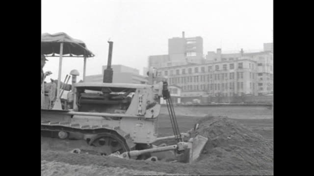 a bulldozer operates at the construction site of the yodobashi purification plant in postwar tokyo. - rebuilding stock videos & royalty-free footage