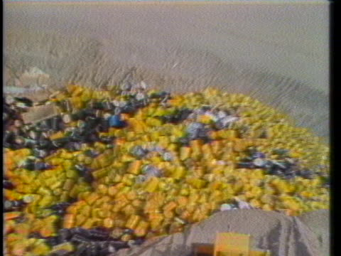 bulldozer pushes earth into a hole containing nuclear waste storage containers at the hanford nuclear waste dump in richland, washington. - 有害廃棄物点の映像素材/bロール