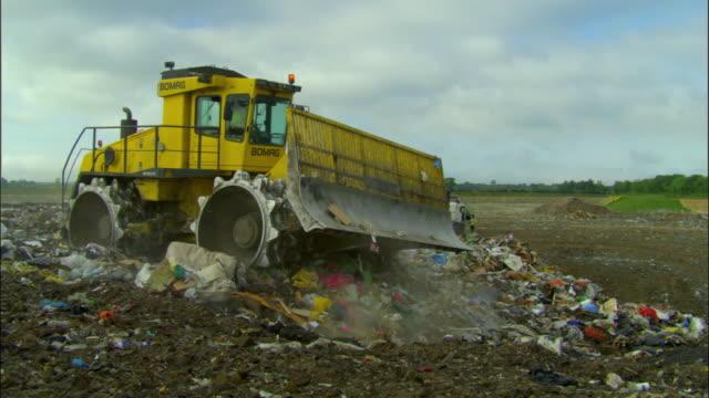 WS, Bulldozer pushing pile of garbage on landfill site, Ardley, Oxfordshire, United Kingdom