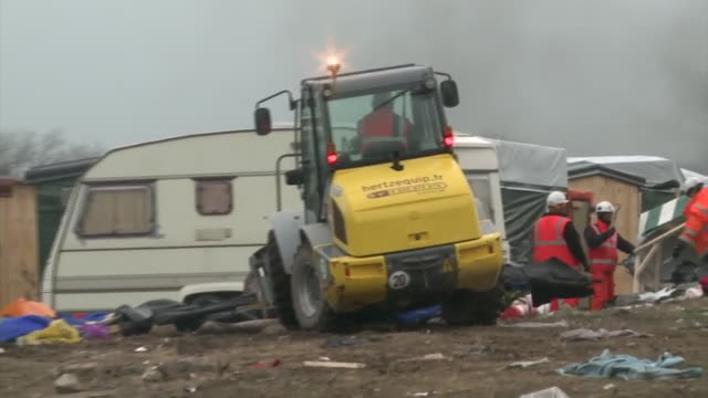 a bulldozer razing makeshift property in the 'jungle' refugee camp in calais - trailer home stock videos & royalty-free footage