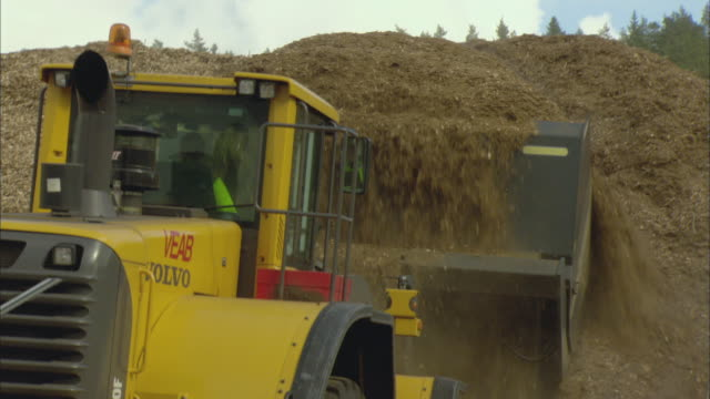 ms tu bulldozer scooping pile of woodchips outside biomass plant / vaxjo, sweden - vaxjo stock videos & royalty-free footage