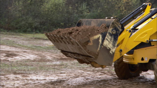 vídeos y material grabado en eventos de stock de a bulldozer scoops dirt and dumps it into a dump truck. - camión de descarga