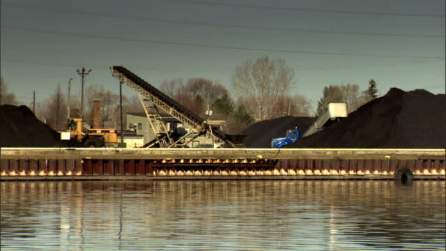 bulldozer & semi truck moving near piles of black coal & coal elevator on bank of fox river, calm waters & bare tree fg. import, export, cargo,... - freight elevator stock videos & royalty-free footage