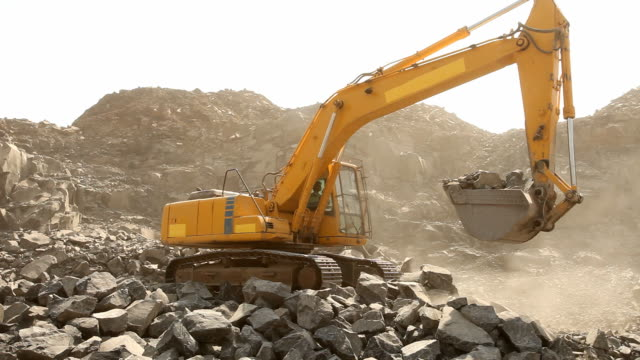 stockvideo's en b-roll-footage met bulldozer working at mining site loading stone on a truck - bouwmachines