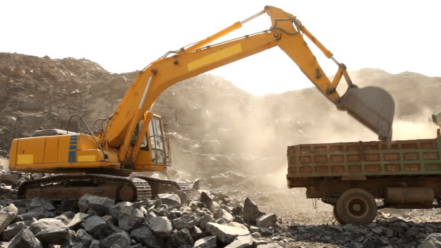 stockvideo's en b-roll-footage met bulldozer working at mining site loading stone on a truck - steen rots