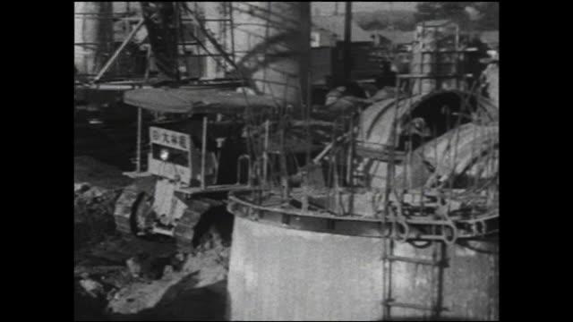 a bulldozer works near a concrete pour at the shinkansen shin-osaka station construction site. - 大阪駅点の映像素材/bロール