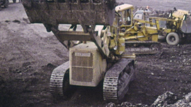 stockvideo's en b-roll-footage met 1969 montage bulldozers removing black shale waste for disposal from chislet colliery / ramsgate, kent, england - schalie