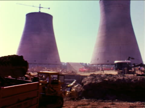 1965 bulldozers working on nuclear power plant construction site / cooling towers in background / PA