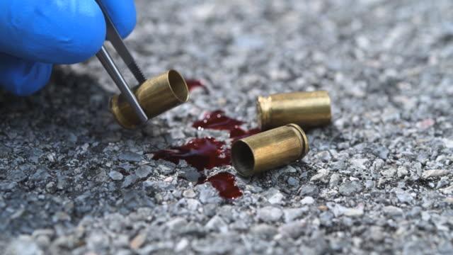 bullet casings on asphalt - forensic science stock videos & royalty-free footage