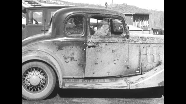 bullet holes in windows and building facade / vs bullet holeriddled older 1920s model coupe automobile used by three robbers to flee police door... - stehlen verbrechen stock-videos und b-roll-filmmaterial
