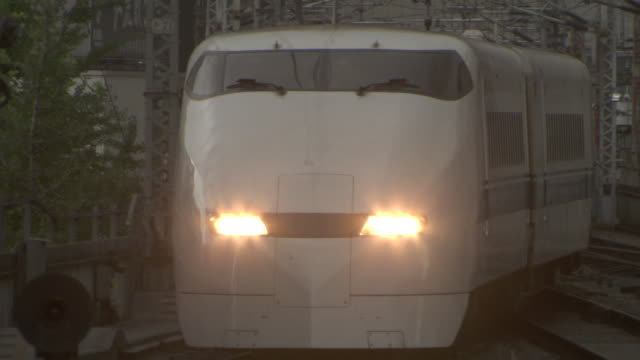 a bullet train arrives at a station with its headlights on. - headlight stock videos & royalty-free footage