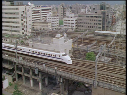 stockvideo's en b-roll-footage met a bullet train moves along an elevated railway in kyoto. - 1990 1999