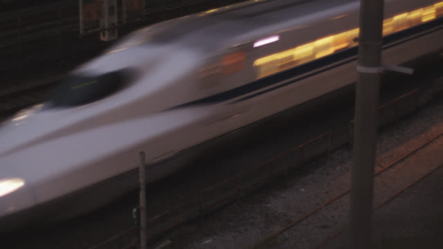 ms bullet train nozomi seven hundred early evening passing through tanmachi station / tokyo, tokyo-to, japan  - passenger train stock videos & royalty-free footage