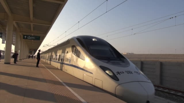 vídeos de stock e filmes b-roll de bullet train stopped at the station platform of turpan north station: evening sun shining over the platform: train leaving the station platform:... - visão frontal