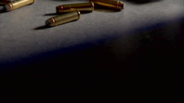 bullets surround a revolver occupying a table. - handgun stock videos and b-roll footage