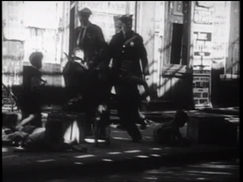 vidéos et rushes de b/w 1939 bully fighting with other children on city sidewalk / nyc / documentary - 1930