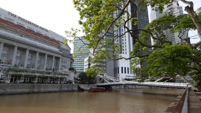 a bumboat makes its way past fullertons hotel at boat quay on february 20 2013 in singapore bumboats were traditionally used to transport supplies to... - river singapore stock videos & royalty-free footage